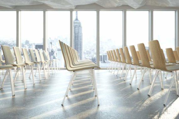 MSM Stapelstuhl Serie 3500 Gestell weiß und Sitzschale Holz Vorderseite gepolstert in großem Seminarraum