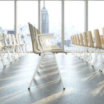 MSM Stapelstuhl Serie 3200 Gestell weiß und Sitzschale Holz Vorderseite gepolstert in großem Seminarraum